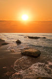 Beautiful sunset above the sea. Sunset above the sea and  stone Stock Images