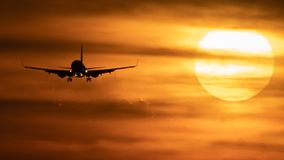 Beautiful sunset with airplane landing and fuel trail. Long shot of huge sun at sunset with airplane landing and fuel trail Royalty Free Stock Photos