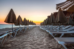 Beautiful sunset in Algarve Portugal.  Beach and cliffs with closed sun umbrellas and sunbeds. Stock Photos