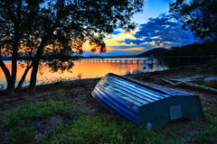 Beautiful Sunset Australia. Beautiful sunset landscape with  blue weathered upturned boat at shoreline at low tide.  This pretty spot is Kincumber, Australia Royalty Free Stock Photos