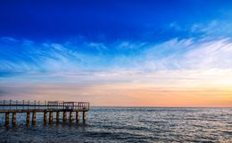 Beautiful sunset in the bay. Clouds of different density and mooring on concrete piles. The sky and water merge on the horizon.  royalty free stock images