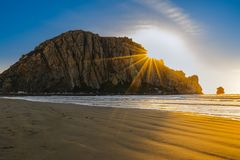 Beautiful sunset on the beach, bright rays from the sun and big rock in the water royalty free stock photo