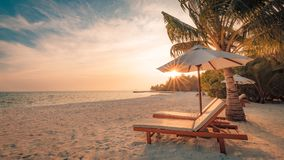 Beautiful sunset beach. Chairs on the sandy beach near the sea. Summer holiday and vacation concept. Inspirational tropical scene. Tranquil beach scene. Exotic stock photo
