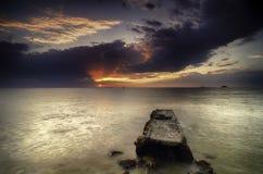 Beautiful sunset at the beach, dramatic dark cloud Royalty Free Stock Image