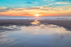 Beautiful sunset at the beach. A beautiful sunset in the fine sand beach during a winter evening Royalty Free Stock Image
