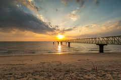 Beautiful sunset at beach with jetty. Malacca, Malaysia Stock Photos