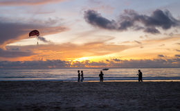 Beautiful sunset on the beach and people taking a parachute in t Royalty Free Stock Photo