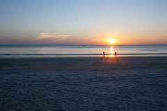 Beautiful sunset on the beach. Silhouette people on sunset background Royalty Free Stock Photo