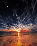 Beautiful sunset on the beach, stars and moon on the sky Stock Photography