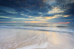 Beautiful sunset at the beach. With waves flowing over Stock Photography