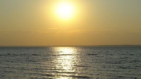Beautiful sunset at beach, waves and seagulls birds flying. Glistening golden ocean, sea surface at sunset or sunrise