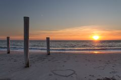 Beautiful sunset at the beach with wooden piles and hearts drawings in the sand. Petten, Holland, North Sea Royalty Free Stock Photo