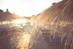 Beautiful sunset on a beautiful sandy beach with sunshades. Royalty Free Stock Image