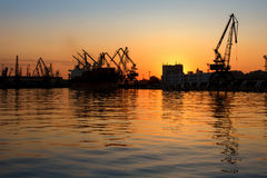Beautiful sunset behind a seaport. Silhouettes of industrial cranes and buildings with reflections in the water. Beautiful sunset behind Seaport Varna, Bulgaria Stock Photos