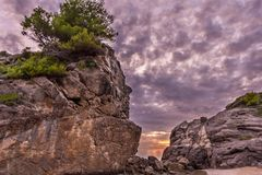 Beautiful sunset and a big rock with trees on top at the coast of central Corfu Greece.  Royalty Free Stock Photography