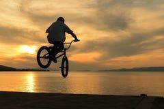 Beautiful sunset and biker's tricks. A beautiful scenery Royalty Free Stock Photo