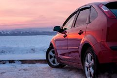 Sunset on a winter river and a car. Beautiful sunset. A car parked near river taken by ice. Sky reflected in the car Royalty Free Stock Image