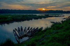 Beautiful sunset in Chitwan National Park, with some boats in a row in the river, yhis beautiful place is mainly covered Royalty Free Stock Photos