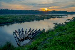 Beautiful sunset in Chitwan National Park, with some boats in a row in the river, yhis beautiful place is mainly covered Stock Photo