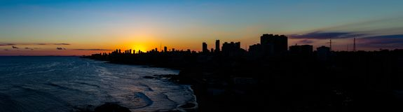 Beautiful sunset in the city of Salvador de Bahia in the northeast of Brazil. Huge buildings cover the sunset. The sea reflects. Light with silver tones royalty free stock photos