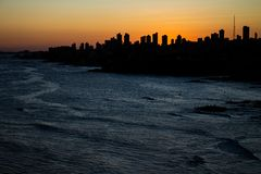 Beautiful sunset in the city of Salvador de Bahia in the northeast of Brazil. Huge buildings cover the sunset. The sea reflects light with silver tones royalty free stock photo