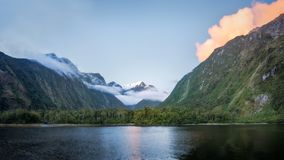 Beautiful sunset color at Harrison Cove in Milford Sound. Colorful sunset clouds over the cliffs in beautiful Harrison Cove at Milford Sound, Fiordland National Stock Images
