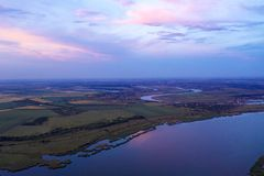 Beautiful sunset in the countryside with a river view shot from the drone. Sunset in different colors shot from a drone in the countryside. The river in the stock image