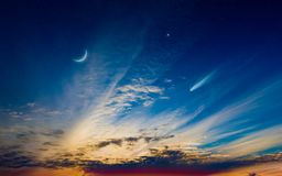 Crescent moon, glowing clouds, comet and bright star. Beautiful sunset with crescent moon, glowing clouds, comet and bright star. Elements of this image royalty free stock photography