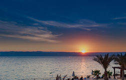 Beautiful sunset at Dead Sea coastline in Jordan. Tropical beach with palm trees and desert plan Royalty Free Stock Photos