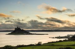 A beautiful sunset with dramatic clouds St Michael`s mount. After a storm passed the dark cloud break up to allow beautiful light from the warm sunset to Stock Photography