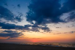Beautiful sunset on an empty sandy beach. Dramatic sky under the sea Stock Photo