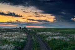 Beautiful sunset is in the field with ground road, wild flowers and grass, sunlight and dark clouds Royalty Free Stock Photos