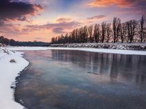 Beautiful sunset on the frozen river. Location Nealezhnosti embankment in Uzhgorod. beginning of the longest European linden alley in winter Royalty Free Stock Image