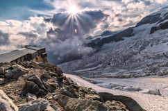 Beautiful sunset on the glacier with alp rifugio. Glacier and refugio at sunset in Alps Royalty Free Stock Image
