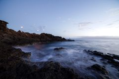Beautiful after sunset glow at rocks at Kaanapali Beach in Maui Hawaii. Beautiful long exposure of waves crashing over the rocks after sunset on Kaanapali Beach royalty free stock photos