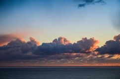 Seascape with beautiful sunset glowing orange under dramatic clouds over the Pacific Ocean royalty free stock photo