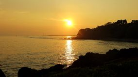 Beautiful sunset with golden sunlight on beach. Video footage of beautiful sunset on the tropical beach with golden sunlight and silhouette of stone stock video