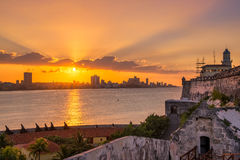 Beautiful sunset in Havana with the sun setting over the seaside buildings. Beautiful sunset in Havana with a view of the city skyline , the El Morro lighthouse Royalty Free Stock Photos