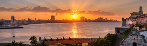 Beautiful sunset in Havana with the sun setting over the seaside buildings. Beautiful sunset in Havana with a view of the city skyline , the El Morro lighthouse Royalty Free Stock Photography