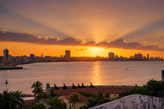 Beautiful sunset in Havana with the sun setting over the seaside buildings. Beautiful sunset in Havana with a view of the city skyline and the sun setting over Stock Photos