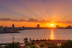 Beautiful sunset in Havana with the sun setting over the seaside buildings. Beautiful sunset in Havana with a view of the city skyline and the sun setting over Stock Photo