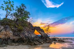 Beautiful sunset in the hole. Of unusual rock wave eroded into the cavity like the arch with a hole in the middle peaceful atmosphere at Hin Thalu Buffalo beach stock images