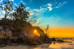 Beautiful sunset in the hole. Of unusual rock wave eroded into the cavity like the arch with a hole in the middle peaceful atmosphere at Hin Thalu Buffalo beach royalty free stock photography