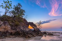 Beautiful sunset in the hole. Of unusual rock wave eroded into the cavity like the arch with a hole in the middle peaceful atmosphere at Hin Thalu Buffalo beach royalty free stock photo