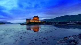 Beautiful sunset at illuminated Eilean Donan Castle over the lake, Scotland stock video footage