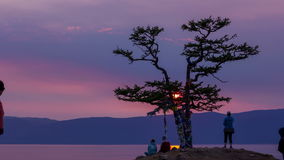 Beautiful sunset on lake Baikal, tree of desire, couple and tourists, timelapse. 4K. Beautiful sunset on the shore of lake Baikal. Tree of desire with colored stock footage