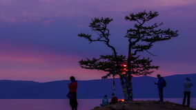 Beautiful sunset on lake Baikal, tree of desire, couple and tourists, timelapse. Beautiful sunset on the shore of lake Baikal. Tree of desire with colored stock footage