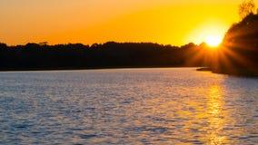 Beautiful sunset on the lake, fishermen on the boat Stock Images