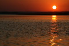 Beautiful Sunset - Landscape. Beautiful sunset shot captured in color in landscape with a clear sky and excellent reflection of the sun on the lake's water Stock Photography