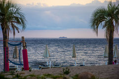 Beautiful sunset landscape with cruising boat on ocean tropical beach with palms sardegna italy royalty free stock photography